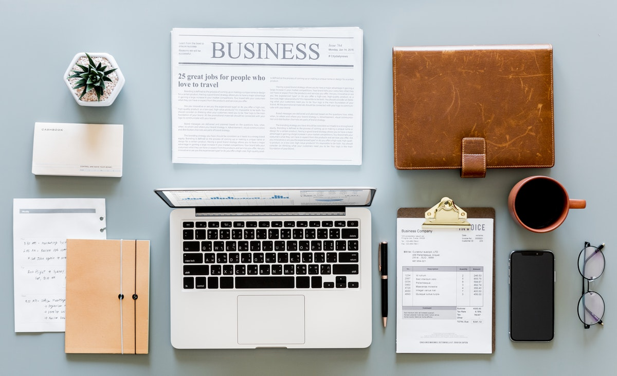 Desk flat lay with computer, business papers and other items